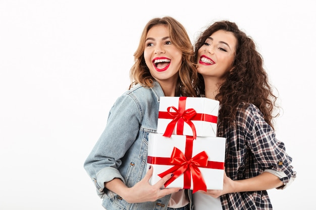Две веселые девушки позируют с подарками и глядя на белую стену Бесплатные Фотографии