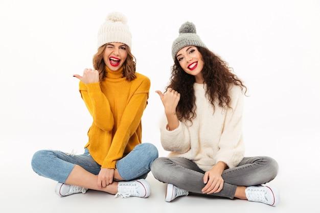 Две игривые девушки в свитерах и шляпах сидят вместе на полу, указывая на белую стену Бесплатные Фотографии