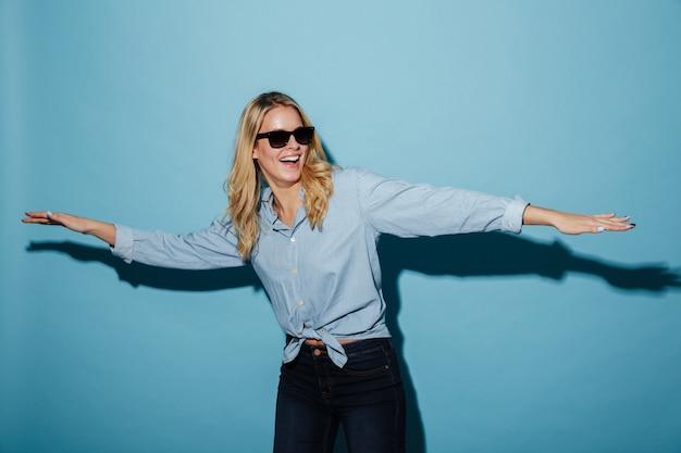 Счастливая шаловливая белокурая женщина в рубашке и солнечных очках смотря прочь Бесплатные Фотографии
