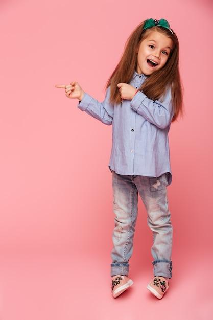テキストまたは製品の面白い少女ジェスチャーポインティング人差し指コピースペースのフルレングスの写真 無料写真