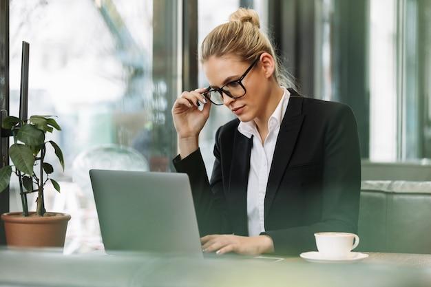 Сконцентрированная белокурая бизнес-леди используя портативный компьютер. Бесплатные Фотографии