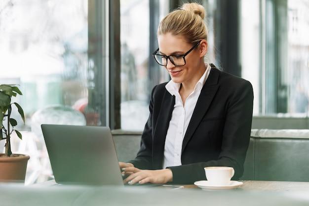 Улыбаясь блондинка бизнес женщина, используя портативный компьютер. Бесплатные Фотографии