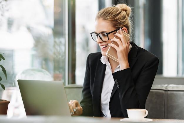 携帯電話で話している笑顔金髪ビジネス女性 無料写真