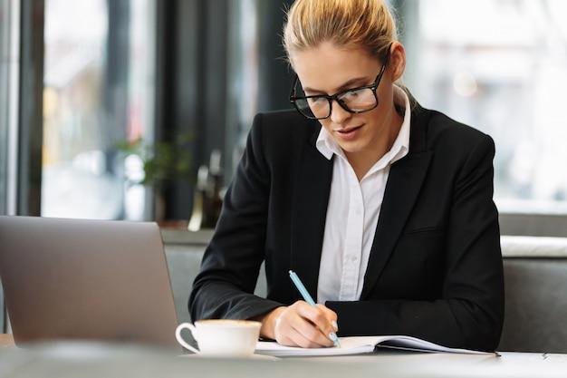 Концентрированный бизнес женщина, написание заметок в записной книжке. Бесплатные Фотографии