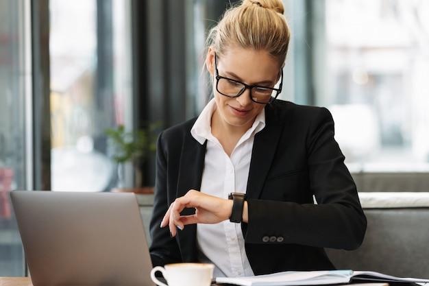 Веселый бизнес женщина смотрит на часы. Бесплатные Фотографии