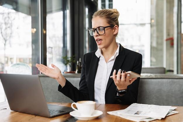 Путать бизнес женщина, используя портативный компьютер и телефон Бесплатные Фотографии