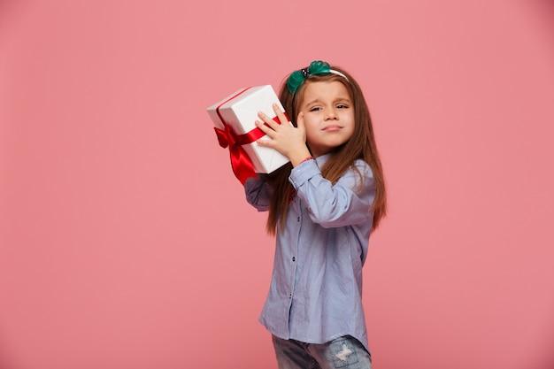 Любопытная девушка трясет подарочную коробочку рядом с ухом, пытаясь определить, что внутри Бесплатные Фотографии