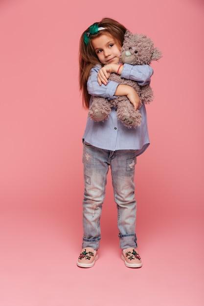 長い赤褐色の髪と彼女の素敵なテディベアを抱き締めるカジュアルな服を着てかわいい子女の子 無料写真