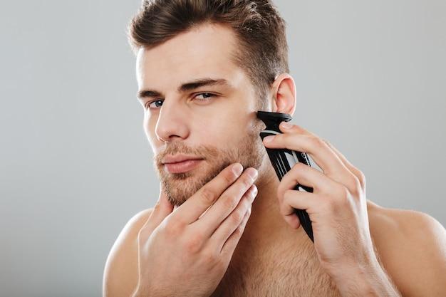 灰色の壁に対してトリマーで顔を剃りながらスキンケアを持つ自宅で服を脱がされている魅力的な男性の男性 無料写真