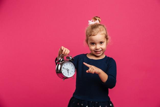 目覚まし時計を押しながらピンクの壁の上のカメラを見ながらそれを指している幸せな若いブロンドの女の子 無料写真