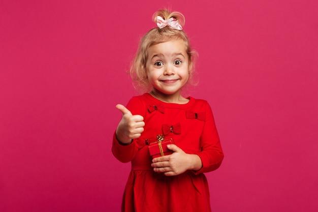 Счастливая молодая блондинка в красном платье, показывая большой палец вверх Бесплатные Фотографии