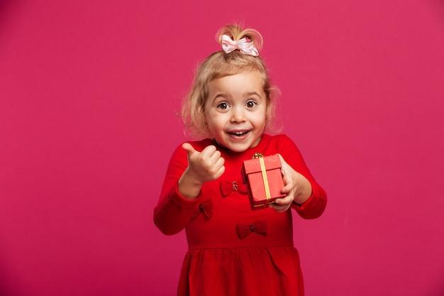 Веселая молодая блондинка в красном платье держит подарочную коробку Бесплатные Фотографии