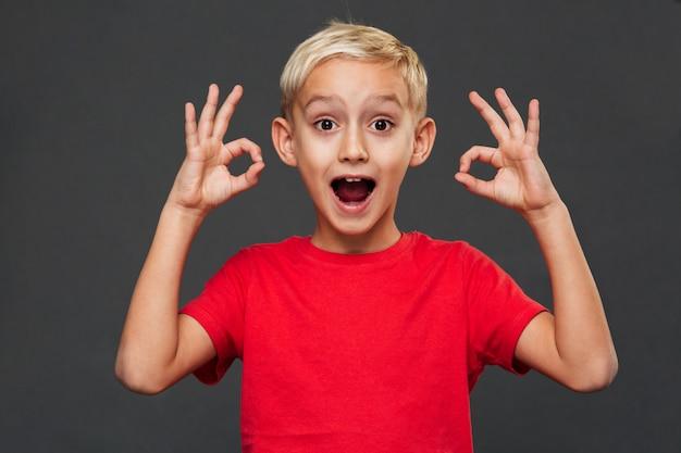 Улыбаясь маленький мальчик, показывая хорошо жест. Бесплатные Фотографии