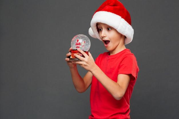クリスマスサンタ帽子をかぶって驚いた小さな男の子 無料写真