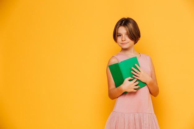 分離された緑の本を保持しているピンクのドレスでかわいい女の子 無料写真