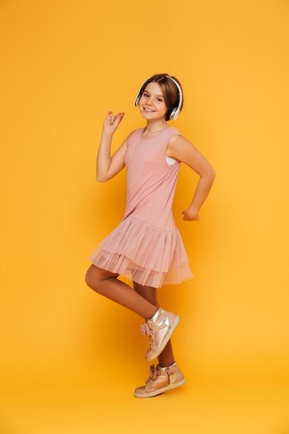 黄色の上に孤立したダンスのヘッドフォンで面白い笑顔の女の子 無料写真