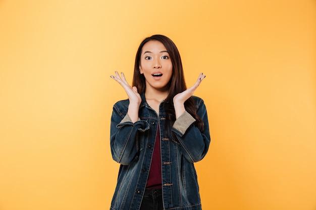 顔の近くの腕を押しながら黄色の背景の上にカメラを見てデニムジャケットで驚くアジア女性 無料写真