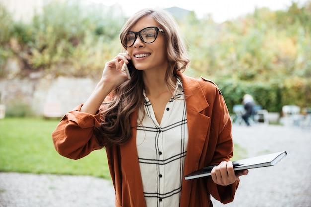 携帯電話で話している幸せな女性の肖像画 無料写真