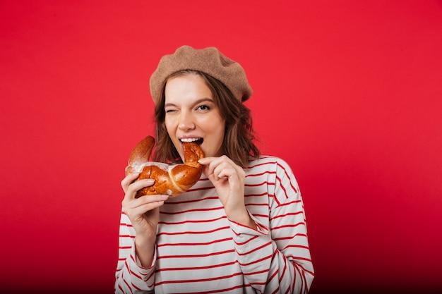クロワッサンを食べるベレー帽を着てきれいな女性の肖像画 無料写真