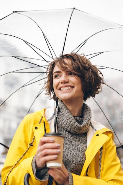 レインコートに身を包んだ陽気な若い女性 無料写真