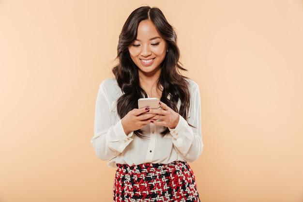 Портрет кормления жизнерадостная женщина прокрутки или чтения текстовых сообщений с помощью своего смартфона на фоне персика Бесплатные Фотографии