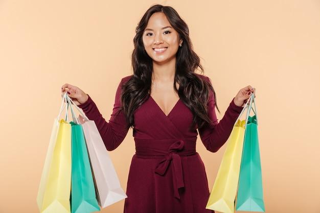 Выстрел из довольной азиатской женщины в довольно бордовом платье позирует на бежевом фоне, держа пакеты с покупками после покупки Бесплатные Фотографии