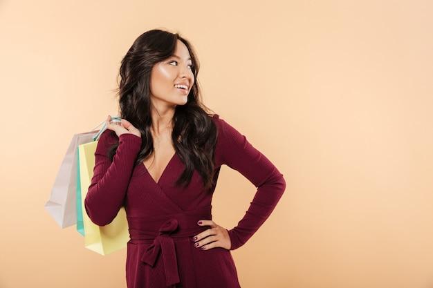 Азиатская молодая женщина с длинными темными волосами, делая покупки, проводя время в торговом центре во время продажи Бесплатные Фотографии