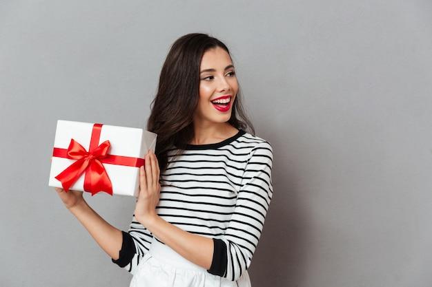 Портрет жизнерадостной девушки с подарочной коробкой Бесплатные Фотографии