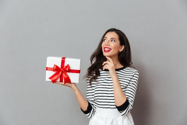 Портрет улыбающейся женщины, держащей подарочную коробку Бесплатные Фотографии