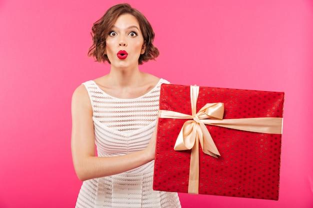 Портрет возбужденной девушки, одетой в платье, держа подарок Бесплатные Фотографии
