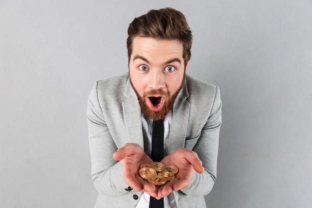 黄金のビットコインを示す満足している実業家の肖像画 無料写真