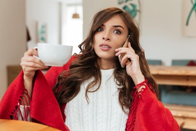 Портрет удивленной женщины разговаривает по мобильному телефону Бесплатные Фотографии