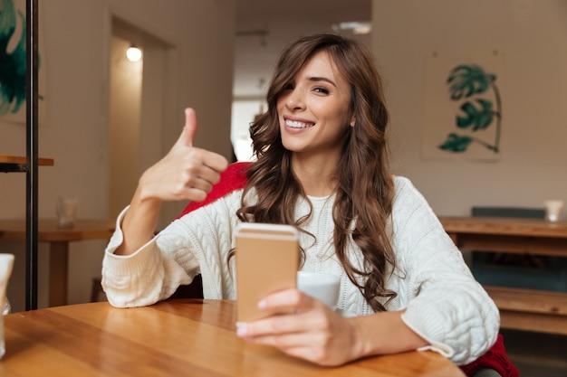 携帯電話を保持しているうれしそうな女性の肖像画 無料写真