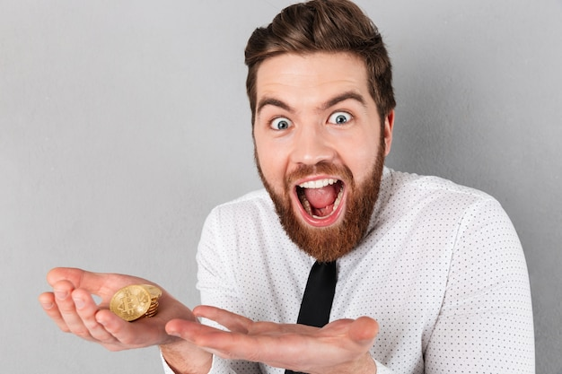 黄金のビットコインを示す興奮している実業家の肖像画 無料写真
