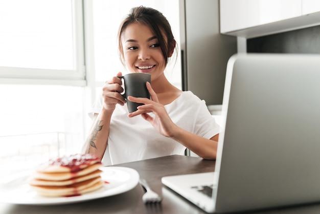 ラップトップを使用して台所に座っている陽気な若い女性 無料写真