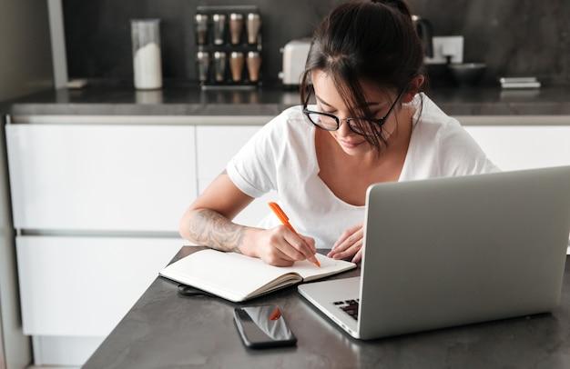 Сконцентрированная серьезная молодая женщина используя примечания сочинительства портативного компьютера. Бесплатные Фотографии