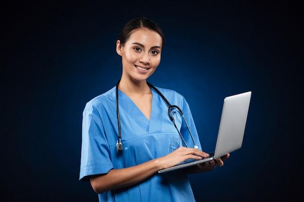 ラップトップを使用して医療制服を着た陽気な女性 無料写真