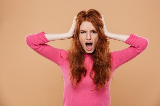 彼女の頭と叫んで彼女の手で動揺して若い赤毛の少女の肖像画を閉じる 無料写真