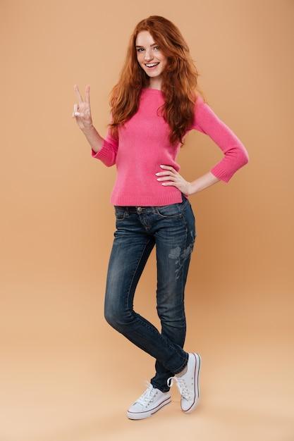 勝利手ジェスチャーで陽気な笑顔赤毛の女の子の完全な長さの肖像画 無料写真