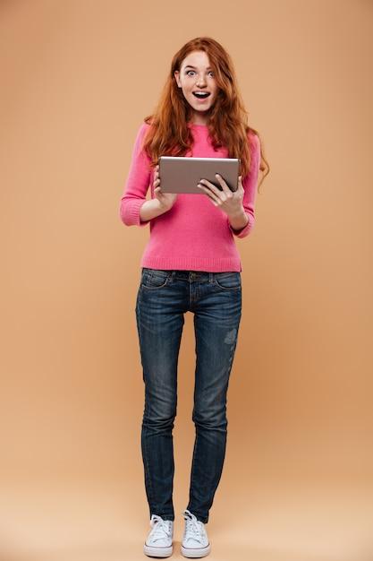 タブレットを保持している興奮したかわいい赤毛の女の子の完全な長さの肖像画 無料写真