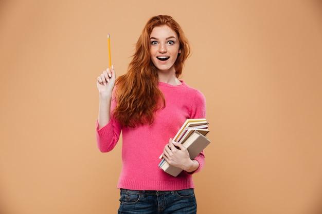 本を保持していると考えて興奮してかわいい赤毛の女の子の肖像画 無料写真