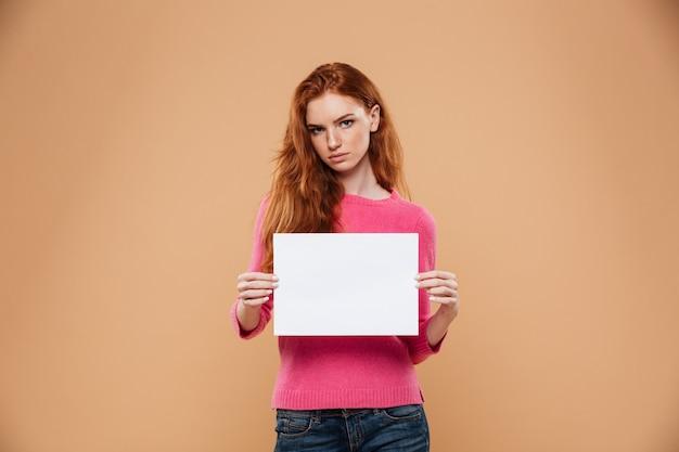 Портрет расстроен довольно рыжая девушка показывает пустой белый плакат Бесплатные Фотографии