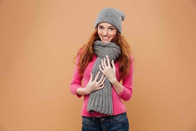 冬の帽子に身を包んだ幸せなかわいい赤毛の女の子の肖像画 無料写真