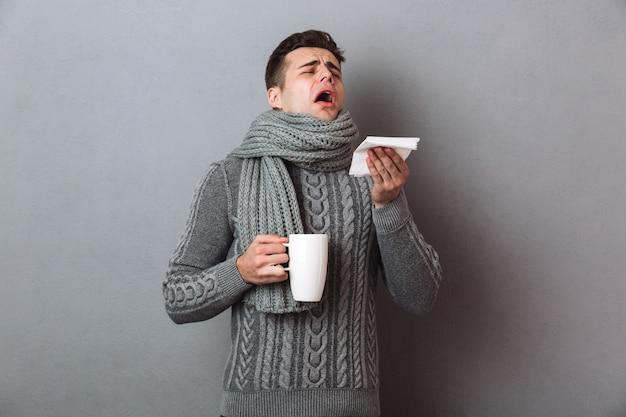 セーターとスカーフで病気の男がお茶を押しながらくしゃみをする 無料写真
