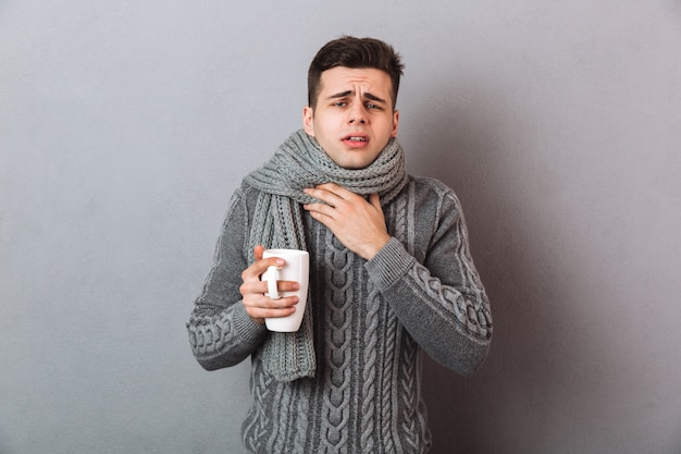 セーターとお茶のカップを押しながら喉の痛みを持つスカーフで病人 無料写真