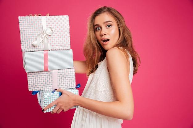 Портрет возбужденной девушки, держащей стопку подарочных коробок Бесплатные Фотографии