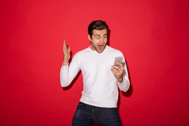 Изображение потрясенного кричащего человека в свитере, смотрящего на смартфон над красной стеной Бесплатные Фотографии
