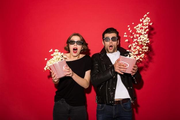 Потрясенная панк-пара разбрасывает попкорн и смотрит Бесплатные Фотографии