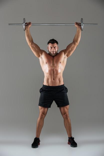 筋肉の深刻な上半身裸の男性のボディービルダーの完全な長さの肖像画 無料写真