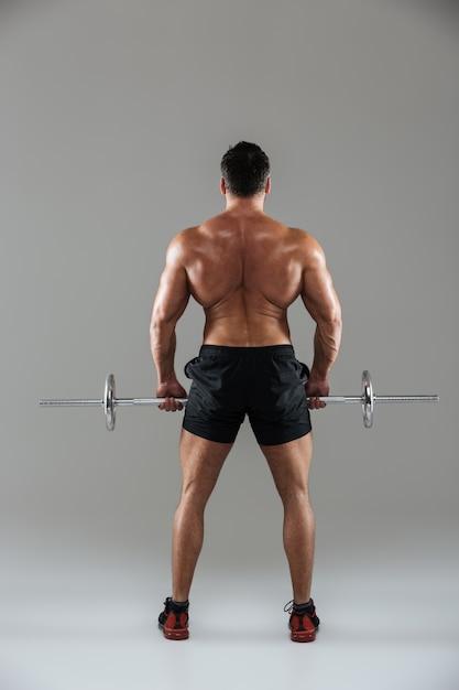 筋肉の上半身裸の男性のボディービルダーの背面図全長 無料写真